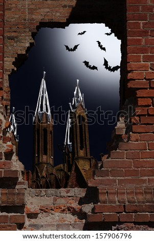 Halloween idea. Night kind through a hole in a wall upon the church and bats in the sky - stock photo