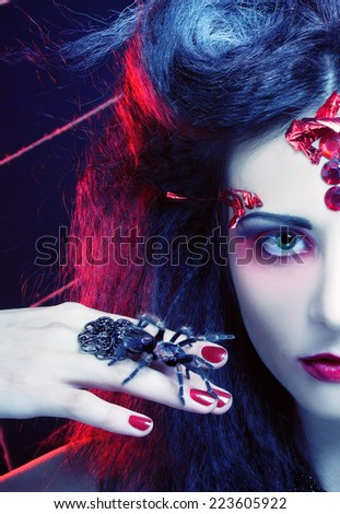 Halloween image. The black widow. Young woman in dark artistic image posing with spider - stock photo