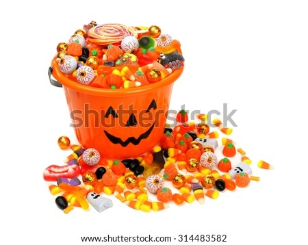 Halloween Jack o Lantern candy pail overflowing with assorted sweets over a white background - stock photo
