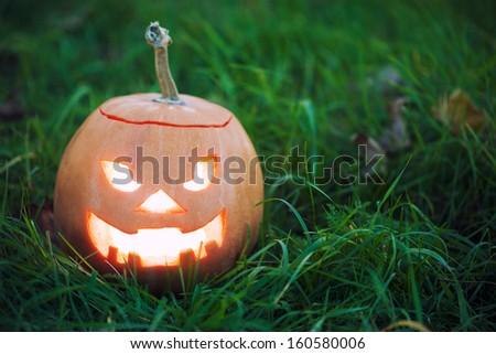 halloween jack-o-lantern on green grass - stock photo
