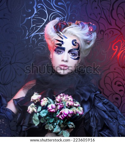 Halloween lady in black. Young woman in creative image and with dry roses. - stock photo
