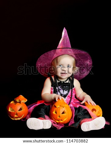 Halloween little girl witch with a carved pumpkin over black background