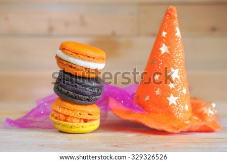 Halloween Macarons in orange and black with witch hat, blur wooden background, for Halloween Party - stock photo