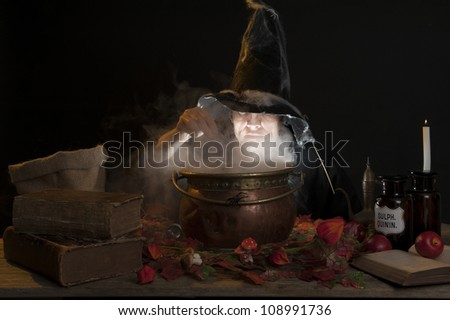 halloween making a potion in a copper cauldron - stock photo