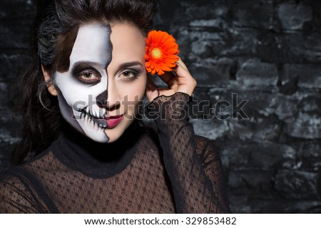 Halloween masquerade party. Close up portrait of a beautiful woman standing with a skeleton make up holding an orange flower near her head and smiling kindly