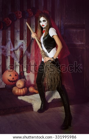 Halloween, mysticism, magic, mystery. Makeup in the style of Billy doll. Witch in a red cloak holding a broom - stock photo