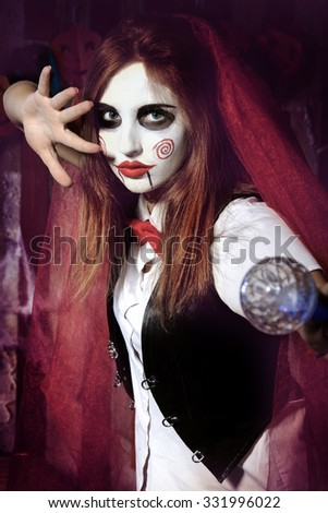 Halloween, mysticism, magic, mystery. Makeup in the style of Billy doll. Witch in a red cloak holding a magic wand - stock photo