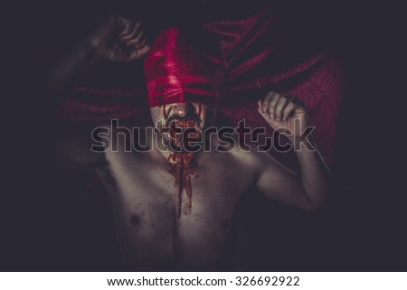 Halloween, naked man on large red cloth over his eyes