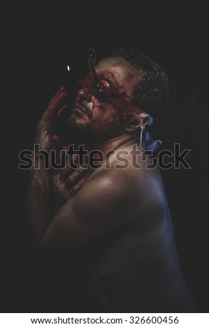 Halloween, naked man with blindfold soaked in blood - stock photo