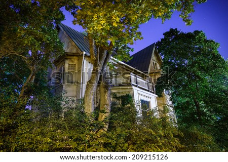 Halloween night at spooky haunted house in Finland. Trees surrounding the house in the moonlight. - stock photo