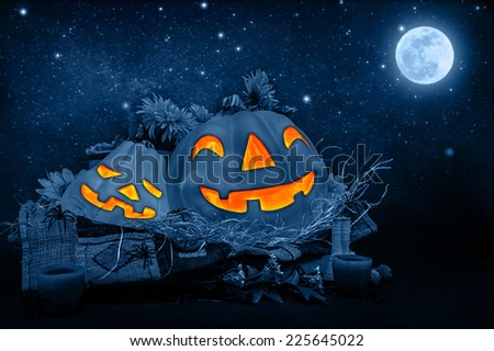 Halloween night decorations, scary carved pumpkin head glowing in dark starry night, full moon, traditional October holiday, horror concept - stock photo