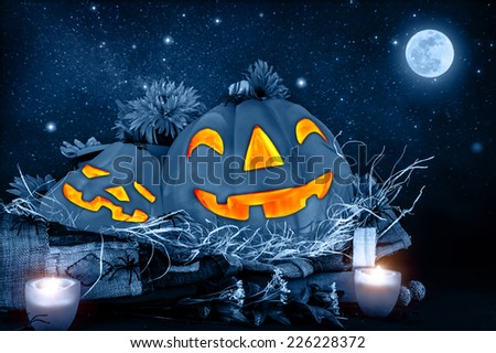 Halloween night, scary carved pumpkin head glowing in dark starry night, full moon, traditional october holiday, horror concept - stock photo