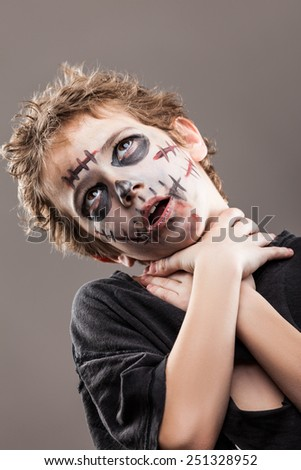 Halloween or horror concept - screaming walking dead zombie child boy reaching hand - stock photo
