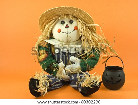 Halloween or Thanksgiving theme straw doll with black pumpkin on orange background - stock photo