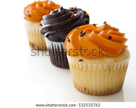 Halloween orange and black cupcakes on white background. - stock photo