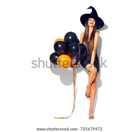 Halloween Party girl. Happy Halloween Sexy Witch with Air balloons. Beautiful young surprised woman in witches hat and short dress holding black and orange air balloons. Isolated on white background.