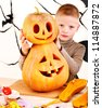 Halloween party with child holding carved pumpkin. - stock