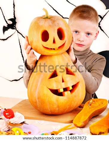 Halloween party with child holding carved pumpkin. - stock photo