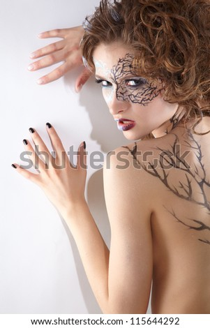 Halloween portrait of beautiful model with skew bodyart and hairdo posing - stock photo