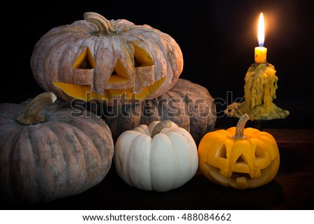 Halloween pumpkin and candle light on the black table in Halloween night / Selective focus