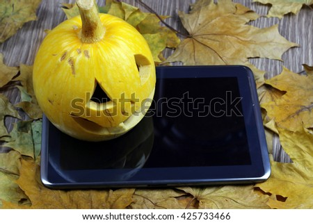 Halloween pumpkin and tablet - stock photo