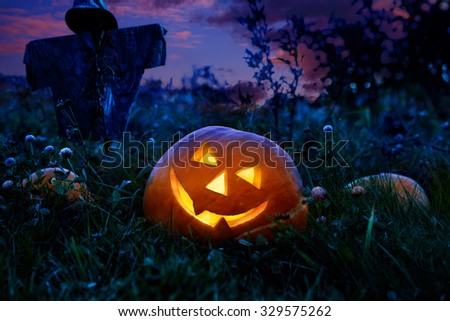 Halloween pumpkin at night lying on a pumpkin field. Against the background of her guards rustic scarecrow. - stock photo