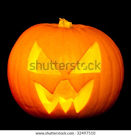 Halloween pumpkin carved with face on black background - stock photo