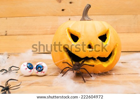 Halloween pumpkin, eyes and spiders - stock photo