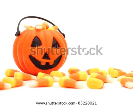Halloween pumpkin filled with candy behind a pile of scattered candy corn on a white background - stock photo