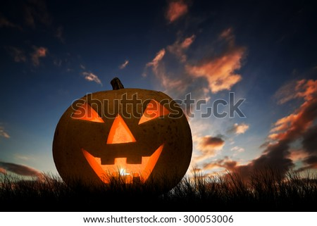 Halloween pumpkin glowing under dark sunset, night sky. Hand carved jack o'lantern with scary face - stock photo