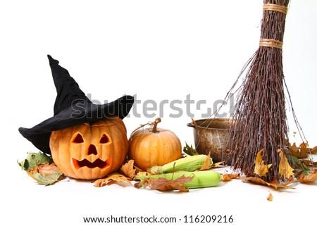 Halloween pumpkin, hat, corn, broom, leaf and pot on the floor - stock photo