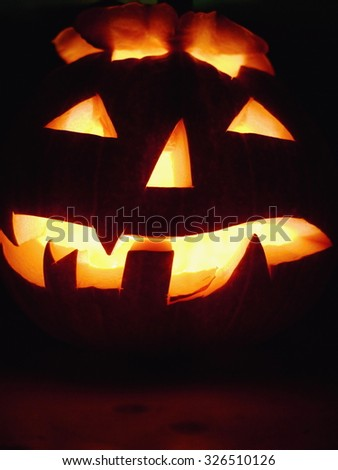 Halloween pumpkin head scary face with evil eye jack spooky and creepy horror lantern - stock photo