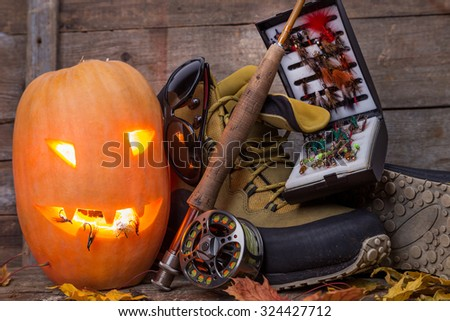 halloween pumpkin head with wading boots and fly-fishing tackles on wooden boards background