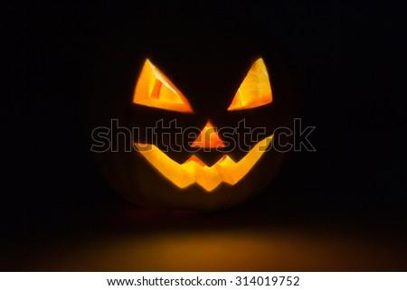 halloween pumpkin Jack O Lantern shiny inside on black - stock photo