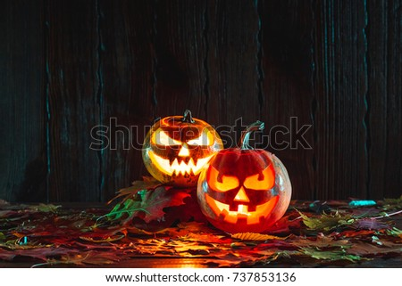 Halloween pumpkin with glowing face on a wooden background with autumn leaves. Idea for flyers, poster, placard, billboard. Free space