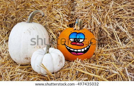 Halloween pumpkin with happy face on hay bales