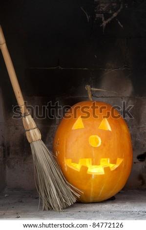 Halloween pumpkin with light in a dark fire place - stock photo