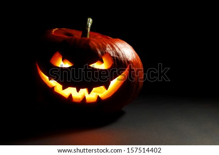 Halloween pumpkin with scary face on black background - stock photo
