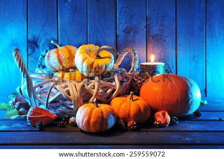 Halloween pumpkins in rattan basket in front of old weathered wooden boards in blue light  - stock photo