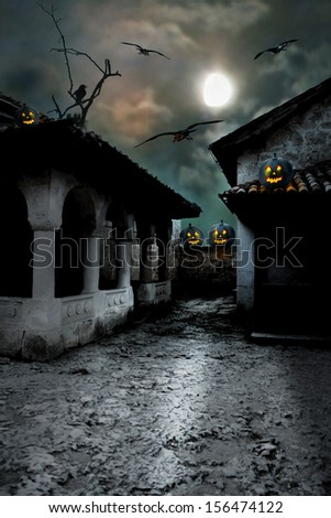 Halloween pumpkins in the yard of an old house at night in the bright moonlight - stock photo