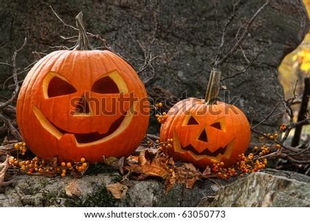 Halloween pumpkins on rocks in an autumn forest - stock photo