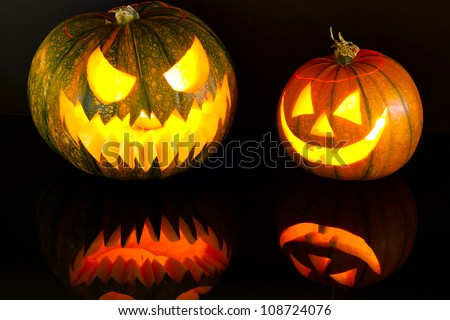 Halloween pumpkins with scary face with reflection - stock photo