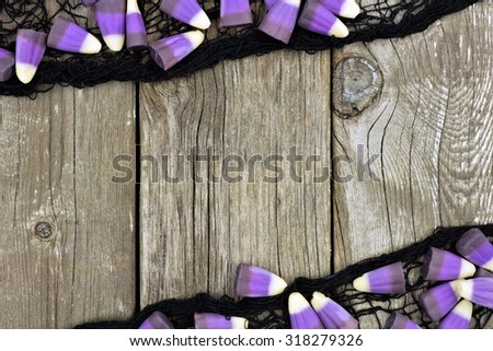 Halloween purple candy corn and black cloth frame against a rustic wood background