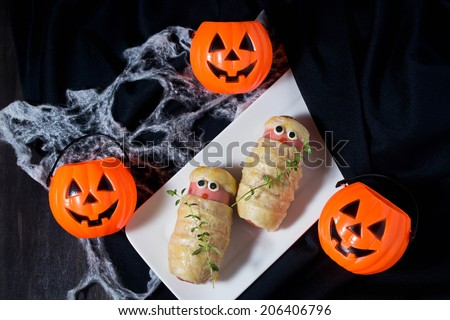 Halloween sausage in the dough decorated to look like mummies - stock photo