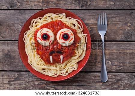 Halloween scary pasta food vampire face with big eyes and moustaches in red dish for celebration party decoration on vintage wooden table background - stock photo