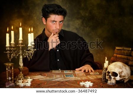 Halloween scene of a young astrologist reading tarot cards - stock photo