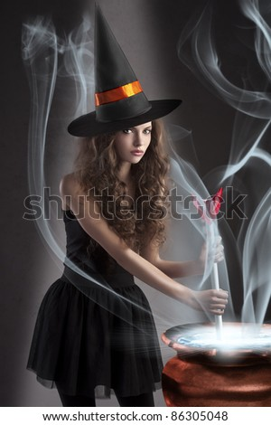 halloween shot of a young and beautiful witch wearing a huge black and orange hat making a poison in a big pot - stock photo