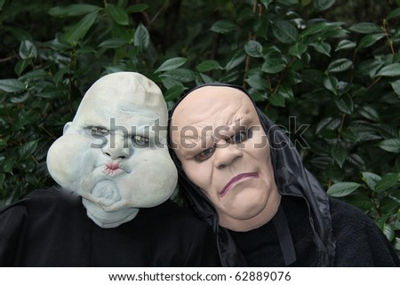 halloween sisters in ugly masks ready to scare - stock photo