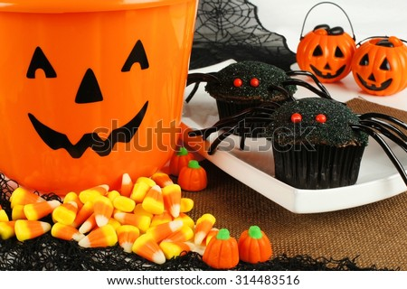 Halloween spider cupcakes with jack o lantern candy pail, candy corn and holiday decor