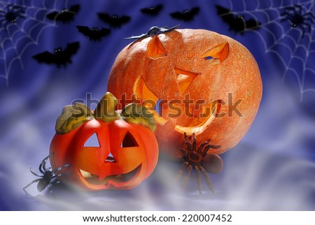 halloween still life with spiders,bats and two pumpkins glowing in autumn night - stock photo